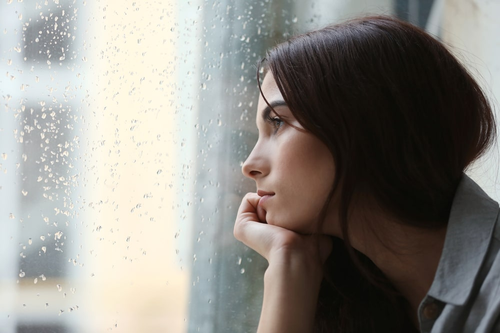 depressed woman looking out the window