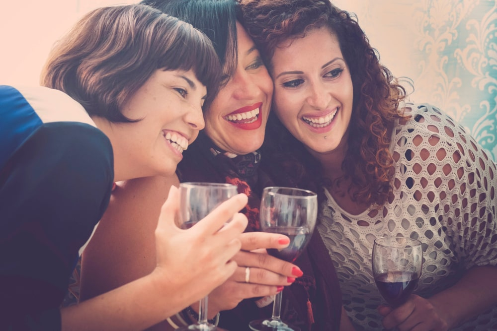 girls laughing and drinking wine
