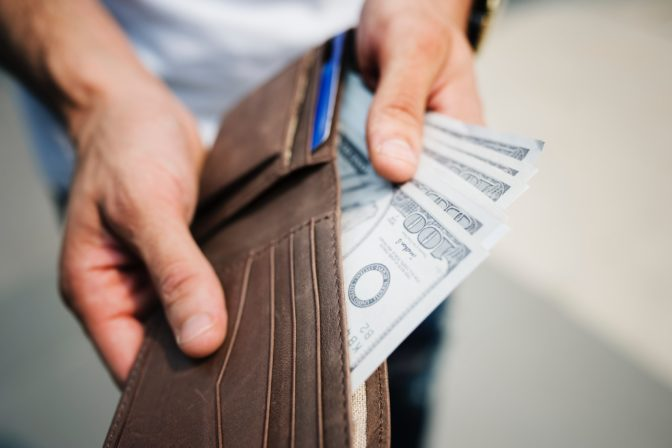 person taking money out of his wallet