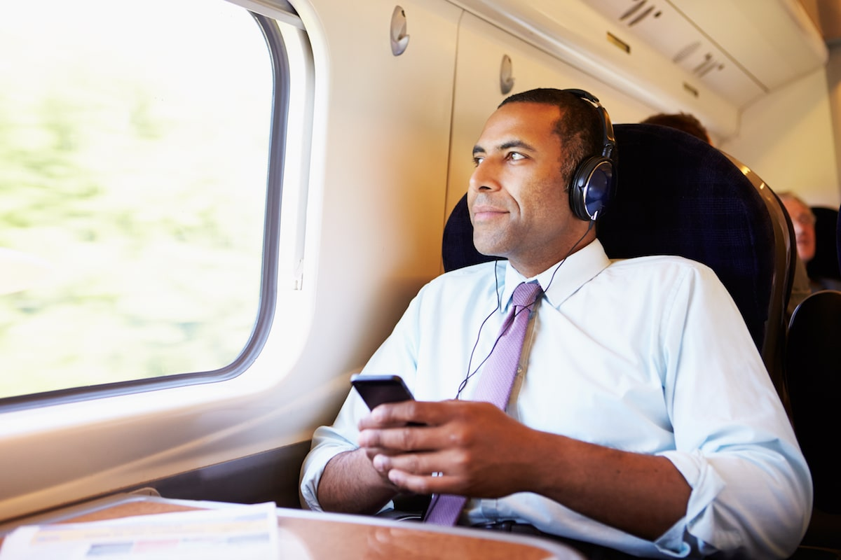 man listening to podcast on train