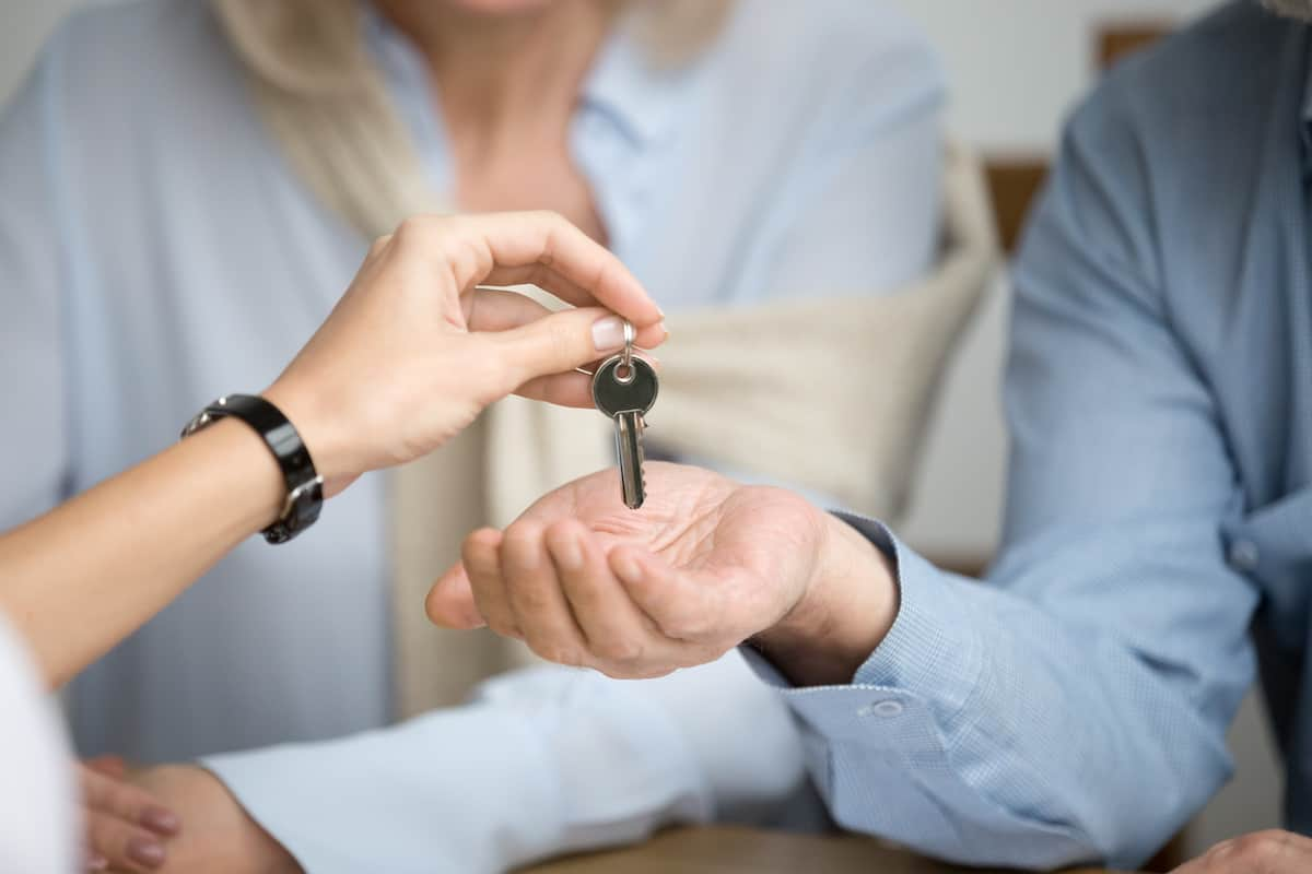 Couple getting handed off the key to their apartment