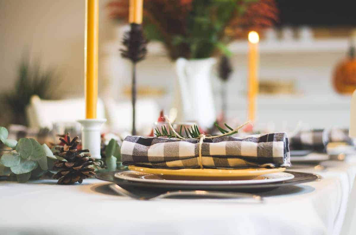 Close up of Thanksgiving table with candles and a rustic place setting