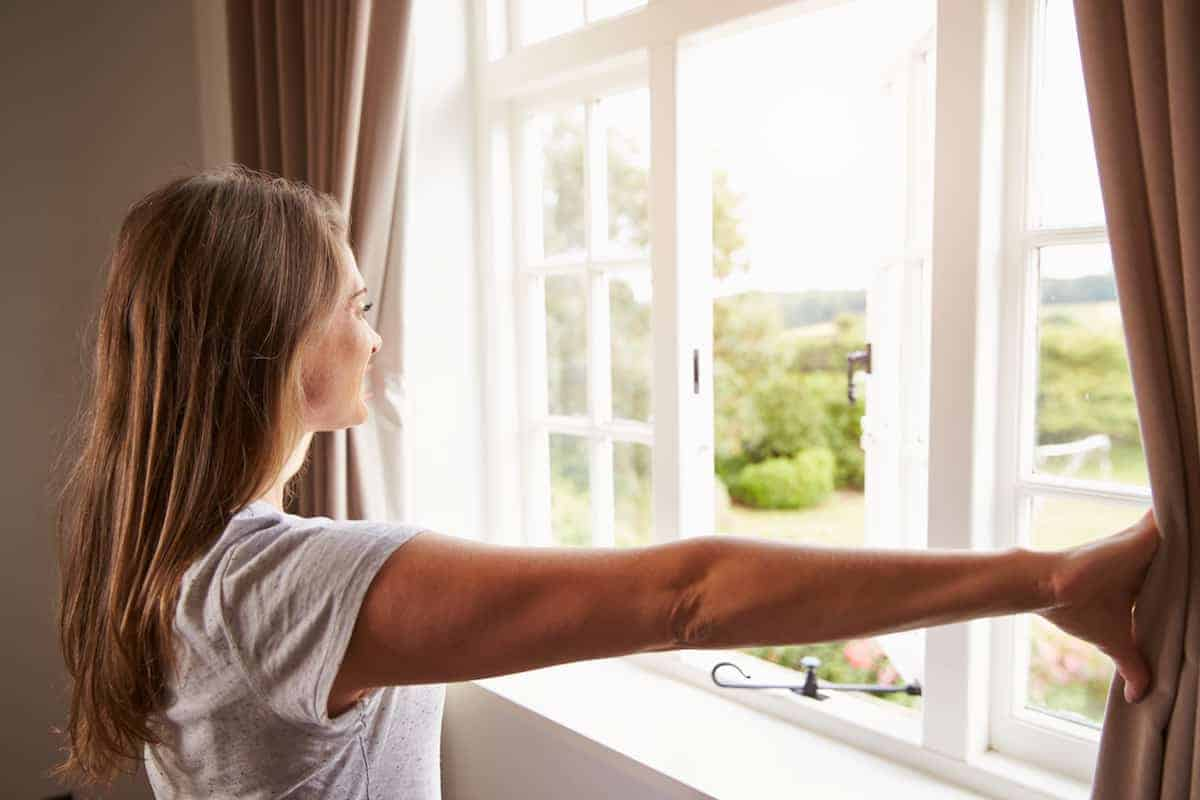 Young woman pulling back curtains on window to let natural light into her apartment