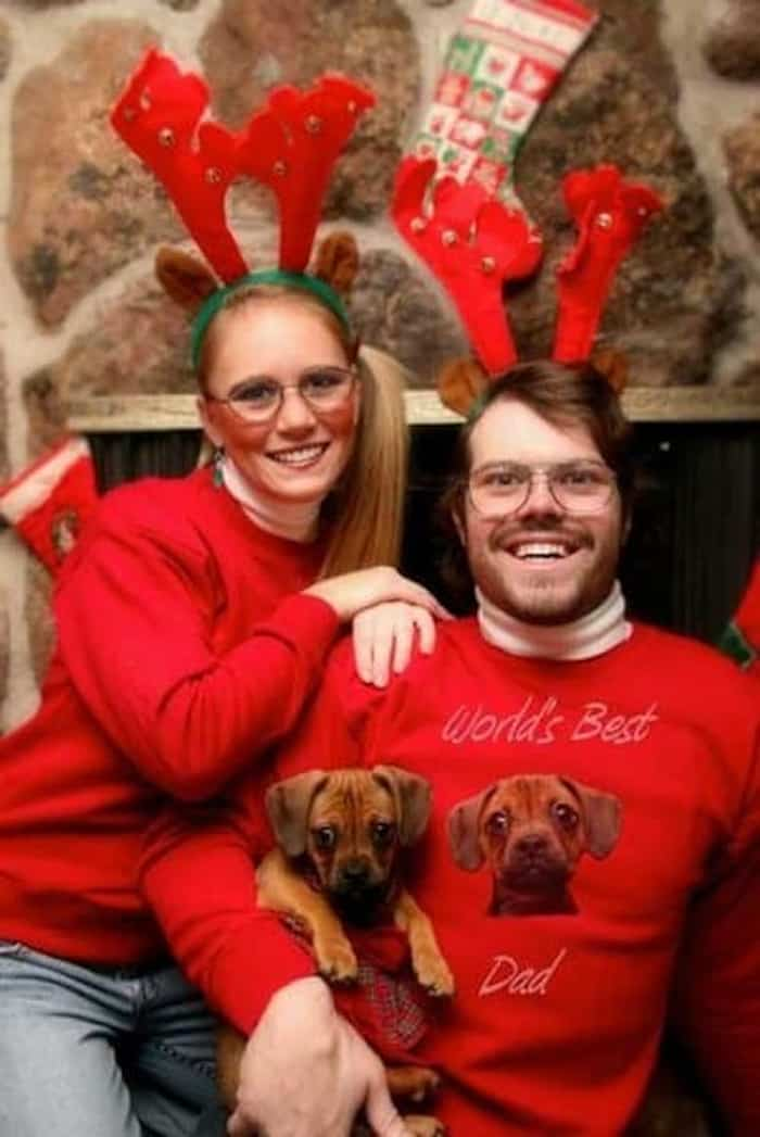 Dog parents with matching sweaters.