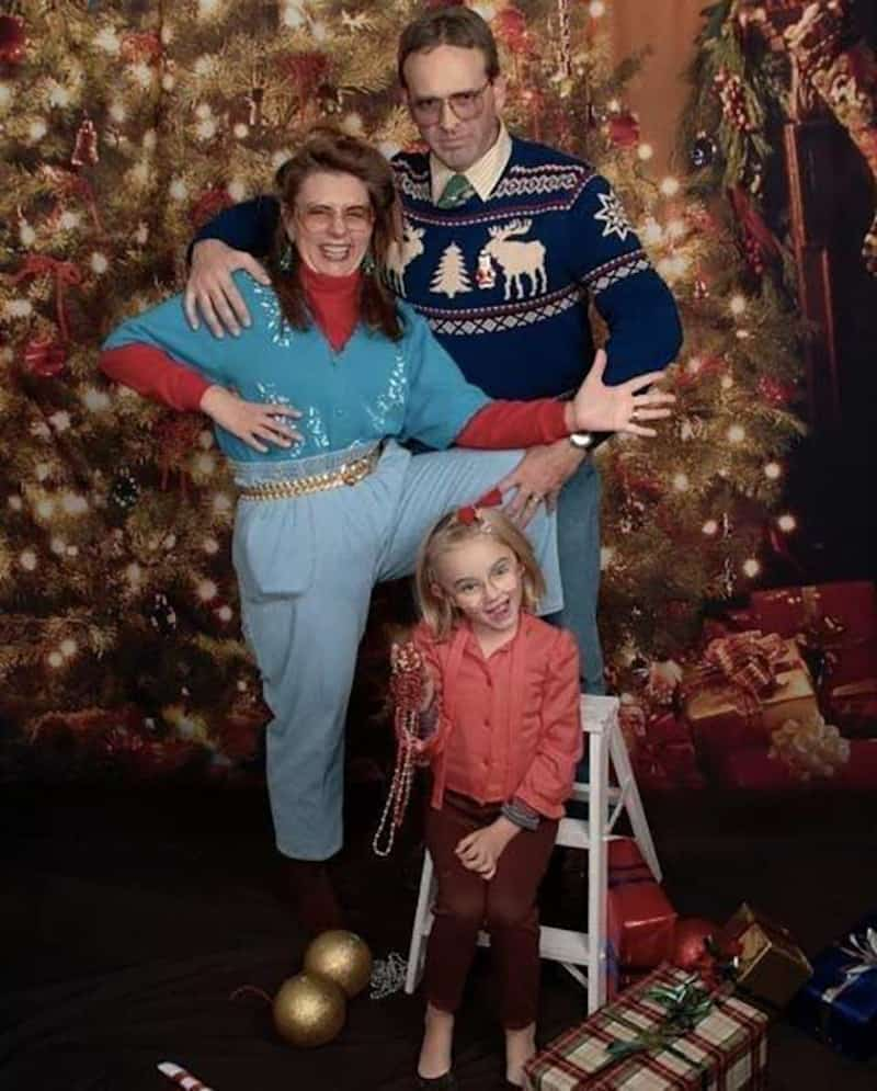 Family striking a pose in front of the Christmas tree.