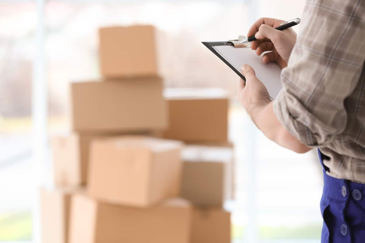 man with checklist and moving boxes