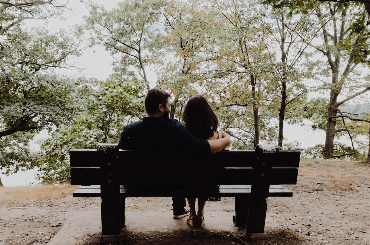 couple on bench talking about moving in together