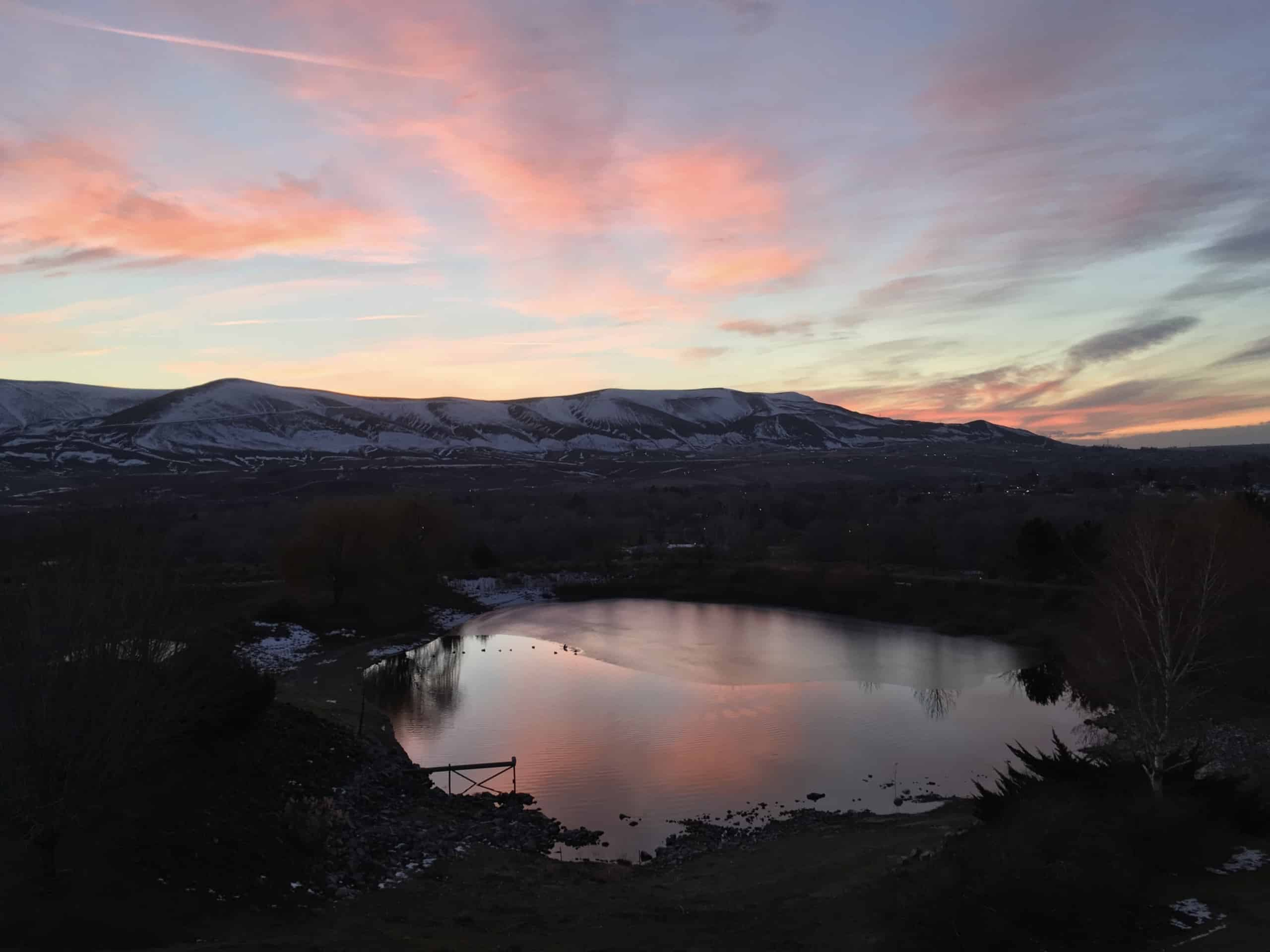 Pink clouds falling over the landscape of mountains and a lake area