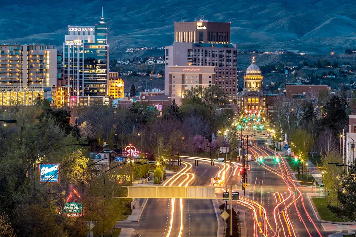 Illuminated lights of the downtown Bosie, ID cityscape as dusk falls zoom towns