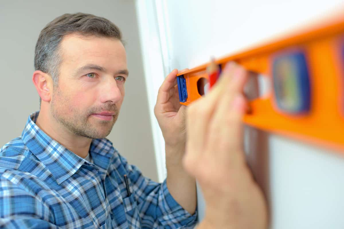 person using a level trying to find a wall stud