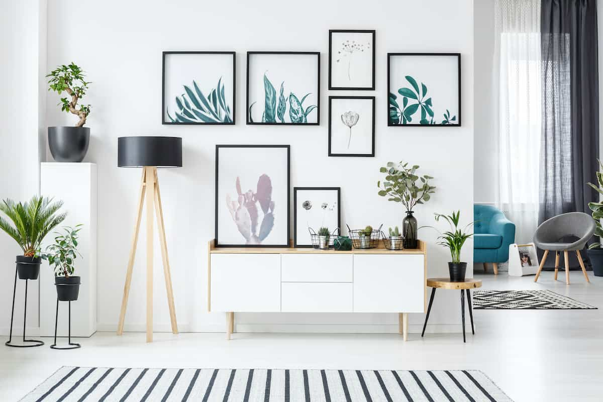 White wall with gallery of colorful framed art pieces, a black and white rug is in front