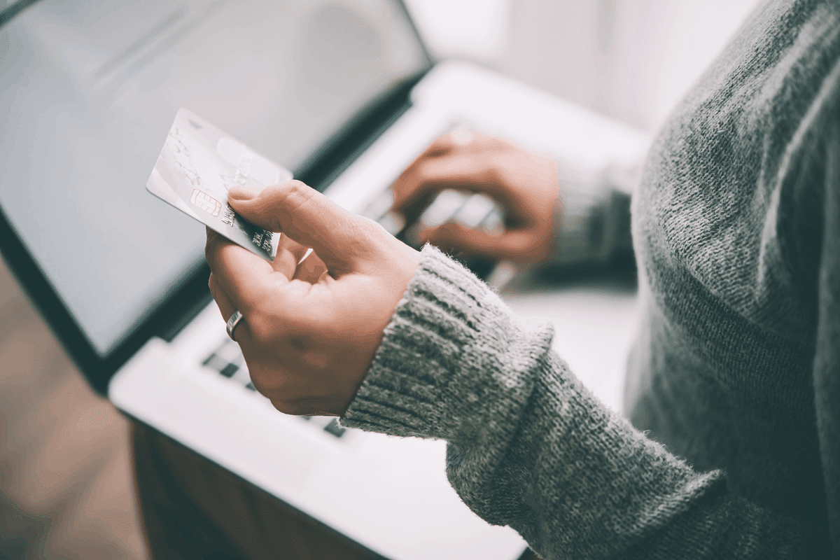 Woman using a laptop and entering in her credit card info.