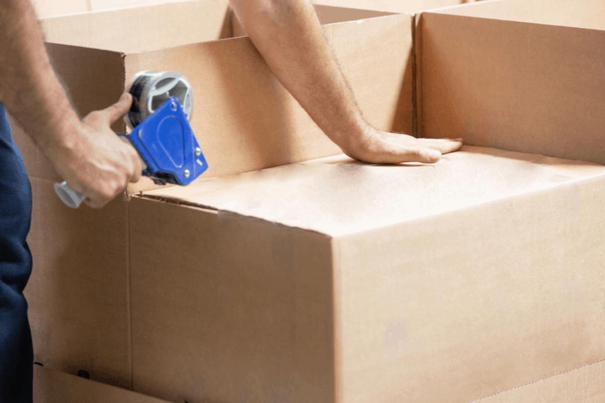 Man taping a moving box.