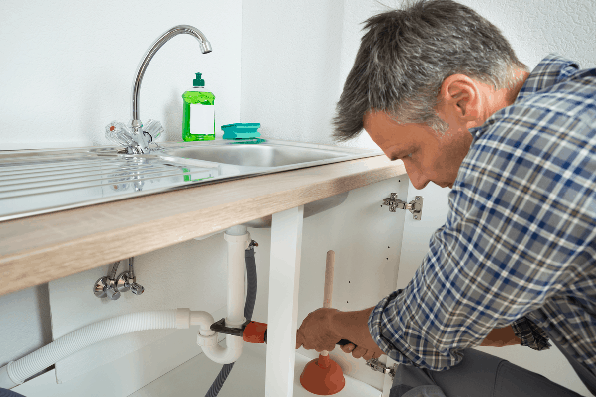 Man repairing a pipe under the sink.