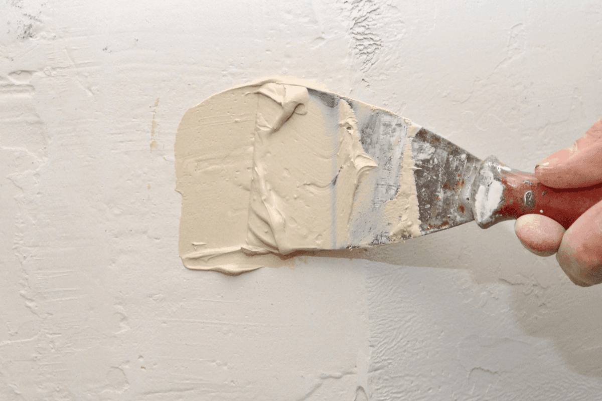 Repairing small holes in the wall with spackle.