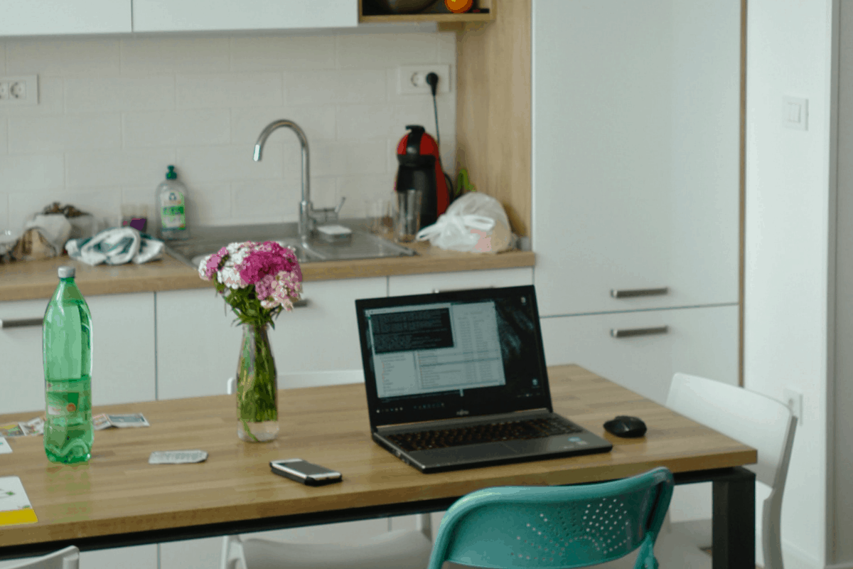 Apartment with a kitchen table that has flowers, a water bottle and a laptop open on it.