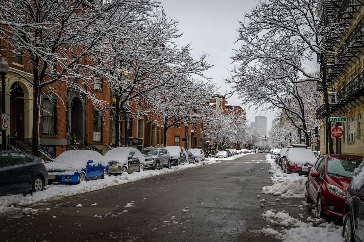 A snow covered street in South End Boston with cars lining both sides.